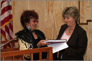 Judy Chicago presenting a Dinner Party book to New Mexico Lt. Governor
